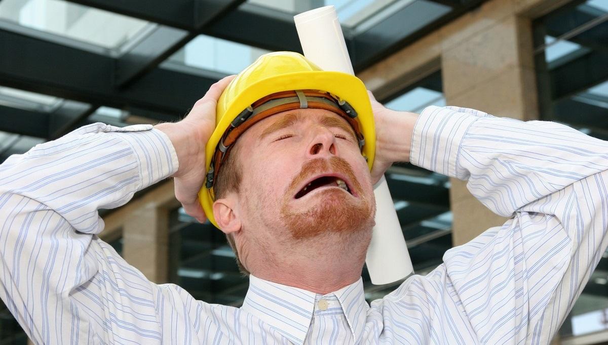 строитель держится за голову
